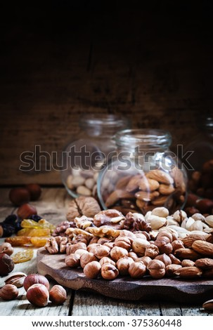 Nuts mix of pistachios, hazelnuts, walnuts and almonds on a wooden platter, selective focus - stock photo