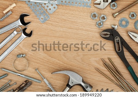 Nuts, screws and bolts closeup on wooden table with copyspace - stock photo