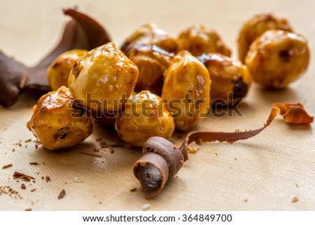 Nuts with caramel and chocolate. hazelnut with caramel closeup. Recipe of caramelized nuts and chocolate macro view. - stock photo