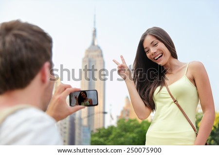 NYC asian chinese tourist girl posing at Empire State Building doing the v hand sign. Young couple of tourists taking pictures with smartphone in New York City in front of famous landmark building. - stock photo
