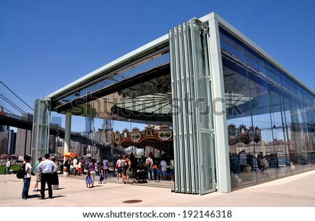 NYC - May 11, 2014:  A contemporary glass pavilion with sliding doors covers the finely restored 19th century James Carousel in Brooklyn Bridge Park - stock photo