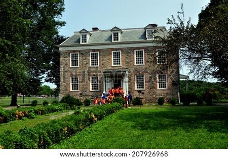NYC (The Bronx) - 29 July 2014:  South front of high Georgian 1748 Van Cortlandt Manor House built in dressed fieldstone with a double-hipped roof and a group of visiting school children - stock photo