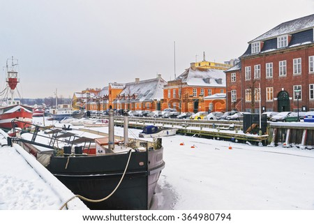 Nyhavn (New Harbor) in winter. It is waterfront, canal, entertainment district in Copenhagen, Denmark. It is lined by colored houses, bars, cafes, wooden ships - stock photo