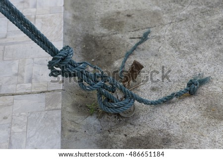 nylon rope tied on steel rod with concrete floor background.