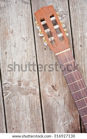 Nylon string guitar neck and headstock on weathered boards - stock photo