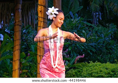 OAHU, HAWAII - DECEMBER 24: Polynesian Cultural Center. Young girl, a student from University of Hawaii in traditional Hawaiian dress performs hula dance on Christmas Eve on December 24, 2008. - stock photo