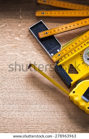 Oak board with wooden meter measuring tape construction level and square ruler construction concept