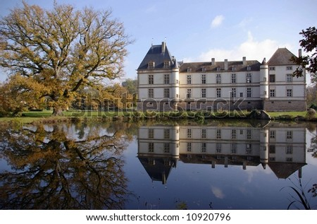 Oak tree and castle reflecting in a pond