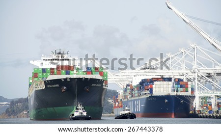 OAKLAND, CA - APRIL 06, 2015: Cargo Ship HATSU COURAGE departing the Port of Oakland with multiple tugboats assisting. Tugboats are vital for safe, efficient entry and exit for the large ships. - stock photo