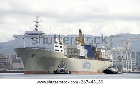 OAKLAND, CA - APRIL 06, 2015: Matson Cargo Ship MANOA entering the Port of Oakland with tugboats Z-FOUR and PATRIOT assisting.