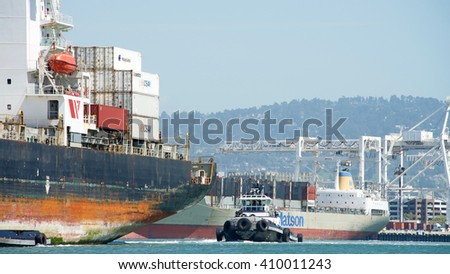 Oakland, CA - April 13, 2016: Tugboat Z-FOUR at the stern of Cargo Ship SEASPAN NINGBO assisting the vessel to maneuver into the Port of Oakland. A tugboat maneuvers vessels by pushing or towing them.