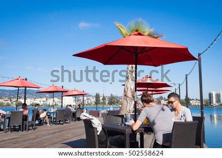 OAKLAND, CA - Aug 25, 2016: People enjoying  weekend  brunch at a Lake Merritt waterfront restaurant with outdoor seating on a wooden dock. Oakland's restaurant scene is booming.