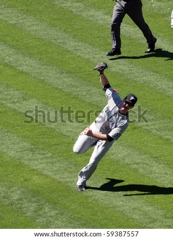 OAKLAND, CA - AUGUST 18: Blue Jays vs. Athletics: Blue Jays Lyle Overbay stands off balance after making a running catch for a fly ball.  Taken on August 18 2010 at Coliseum in Oakland California.