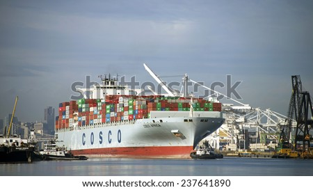 OAKLAND, CA - DECEMBER 14, 2014: Cargo Ship COSCO AFRICA is turned in the Port of Oakland's Inner Harbor with Tugboat PATRICIA ANN pulling from the Port Bow MARSHALL FOSS pushing on the Starboard Bow.