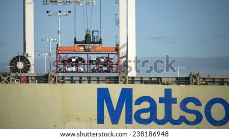 OAKLAND, CA - DECEMBER 16, 2014:  Matson Cargo Ship MANOA loading at the Port of Oakland loading new motor vehicles loaded on car carriers in addition to standard Shipping Containers. - stock photo