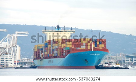Oakland, CA - December 13, 2016: Multiple tugboats push and pull cargo ship GERD MAERSK to turn the vessel prior to docking at the Port of Oakland.