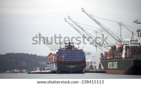 OAKLAND, CA - DECEMBER 17, 2014: Tugboats VETERAN, VALOR  and REVOLUTION at Port bow, side and quarter, work cohesively to insert APL Cargo Ship PHILIPPINES between Cargo Ships at the Port of Oakland.
