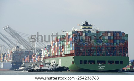 OAKLAND, CA - FEBRUARY 19, 2015: China Shipping Container Line Cargo Ship SPRING entering the Port of Oakland. Four tugboats worked in tandem to push the behemouth vessel sideways to the dock. - stock photo