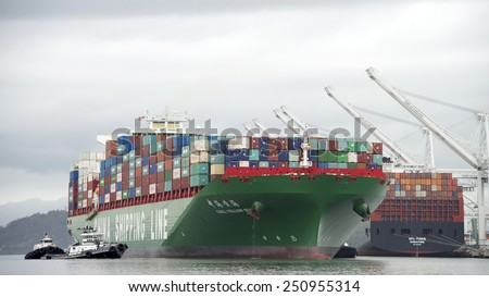 OAKLAND, CA - FEBRUARY 07, 2015: CSCL Cargo Ship YELLOW SEA, built in 2014, has a Gross Tonnage of 116,568. The vessels size necessitates the use of Four Tugboats to assist it to the Port of Oakland. - stock photo