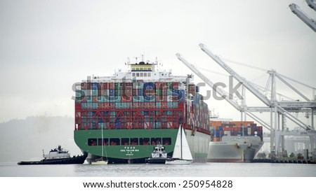 OAKLAND, CA - FEBRUARY 07, 2015: Multiple Tugboats assist CSCL Cargo Ship YELLOW SEA into the Port of Oakland. Tugs move vessels that should not move themselves, such as ships in a crowded harbor. - stock photo