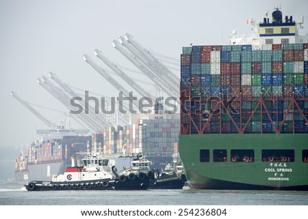 OAKLAND, CA - FEBRUARY 19, 2015: Newer Cargo Ships are larger than ever and are unable to maneuver sideways. Four tugboats work in tandum to maneuver CSCL SPRING to the dock at the Port of Oakland. - stock photo