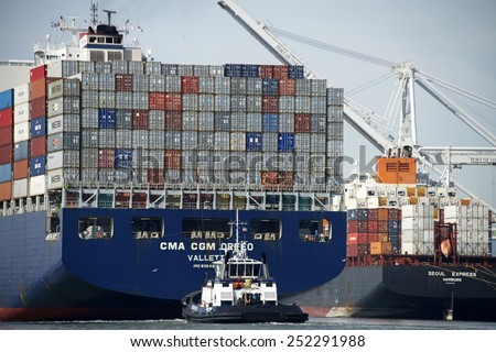 OAKLAND, CA - FEBRUARY 12, 2015: Tractor Tugboat AHBRA FRANCO at the Stern of CMA CGM Cargo Ship ORFEO as it enters the Port of Oakland. A tugboat maneuvers vessels by pushing or towing them. - stock photo