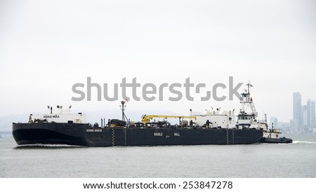 OAKLAND, CA - FEBRUARY 17, 2015: Tugboat ROYAL MELBOURNE pushing the Barge BERNIE BRIER, a double hulled vessel, into the Middle Harbor at the Port of Oakland. - stock photo