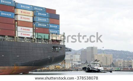 OAKLAND, CA - FEBRUARY 17, 2016: Tugboat Z-FIVE at the stern of Cargo Ship HANJIN UNITED KINGDOM, assisting the vessel to maneuver out of the Port of Oakland. City of Oakland in background.