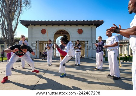 OAKLAND, CA-JAN 3, 2015: Capoeira martial arts practice at Lake Merritt Park in downtown Oakland. Brazilian with African roots, Capoeira combines acrobatics, dance and music, with spins and kicks. - stock photo