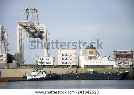 OAKLAND, CA - JANUARY 05, 2014: Foss POINT FERMIN with a barge ship next to Matson Cargo Ship MAUI. Workers provide maritime services while the ship unloads and loads cargo at the Port of Oakland.