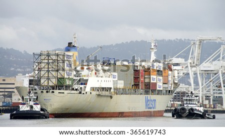 OAKLAND, CA - JANUARY 18, 2016: Matson Cargo Ship MAUI entering the Port of Oakland with tugboat assistance. The Port of Oakland is the fifth busiest container port in the United States.
