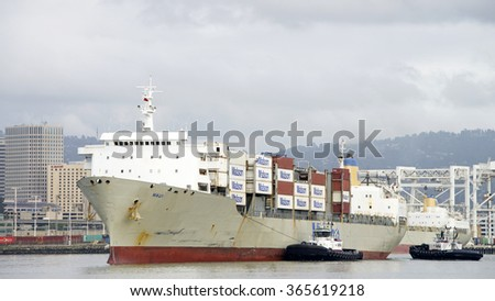 OAKLAND, CA - JANUARY 18, 2016:  Matson Cargo Ship MAUI entering the Port of Oakland with tugboats assisting. Matson provides shipping services Pacific wide. Mainly to and from the Hawaiian Islands.