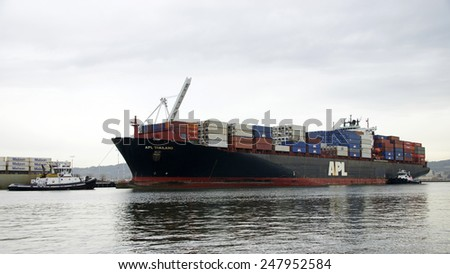 OAKLAND, CA - JANUARY 27, 2015: Tugboats DELTA CATHERYN and VETERAN guide APL THAILAND into the Port of Oakland. Tugs move vessels that should not move themselves, such as ships in a crowded harbor.