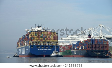 OAKLAND, CA - JANUARY 04, 2014: Tugboats move vessels that should not move themselves, such as ships in a crowded harbor. Multiple Tugboats escort CMA CGM Cargo Ship CENTAURUS from the Port of Oakland - stock photo