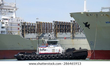 OAKLAND, CA - JUNE 04, 2015: AmNav Tugboat REVOLUTION at the bow of Matson Cargo Ship MOKIHANA, assisting the vessel to maneuver out of the Port of Oakland.
