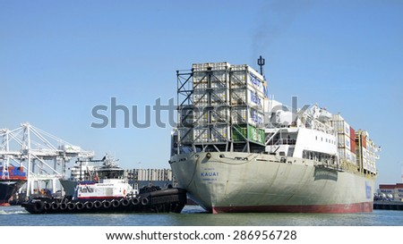 OAKLAND, CA - JUNE 08, 2015: AmNav Tugboat REVOLUTION pushing on the stern of Matson Cargo ship KAUAI, turning the vessel 180 degrees and up to the dock at the Port of Oakland.