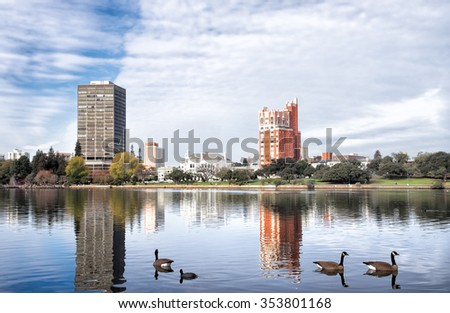 Oakland, Ca Lake Merritt. View of waterfront buildings across the lake. Canadian geese swimming in the foreground - stock photo