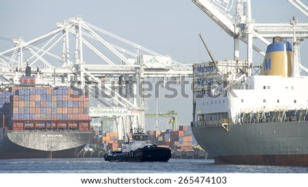 OAKLAND, CA - MARCH 30, 2015: AmNav Tugboat REVOLUTION at the stern of Matson Cargo Ship MAUI as it enters the Port of Oakland. A tugboat maneuvers vessels by pushing or towing them.