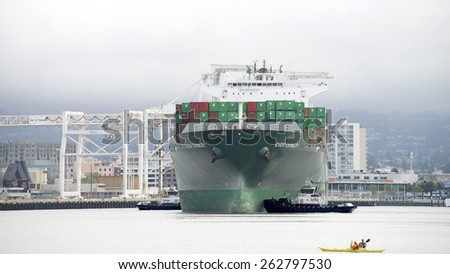 OAKLAND, CA - MARCH 22, 2015: Evergreen Cargo Ship EVER CHIVALRY departing the Port of Oakland. Multiple tugboats rotate the vessel in the Middle Harbor while Kayakers  watch - stock photo