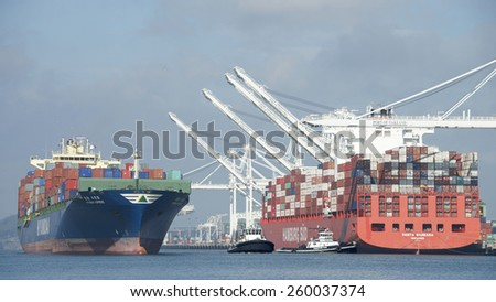 OAKLAND, CA - MARCH 11, 2015:  HYUNDAI SUPREME Cargo Ship entering the Port of Oakland Middle Harbor passing Hamburg SUD Cargo Ship SANTA BARBARA as it prepares for departure. - stock photo