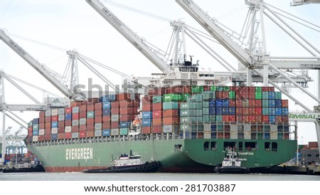 OAKLAND, CA - MAY 22, 2015: Cargo Ships are usually unable to maneuver sideways. Multiple tugboats push EVER CHAMPION sideways to the docks at the Port of Oakland.