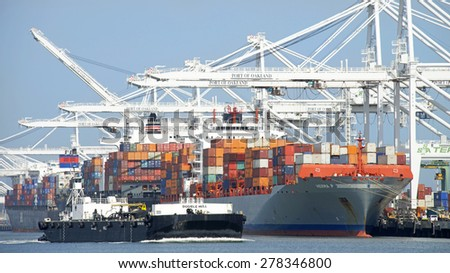 OAKLAND, CA - MAY 06, 2015: Tugboat pushing a double hulled barge ship past the Port of Oakland. Tugboats are powerful for their size and strongly built. - stock photo