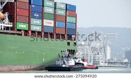 OAKLAND, CA - MAY 03, 2015: Tugboats REVOLUTION and VALOR assisting Cargo Ship CSCL SPRING into the Port of Oakland.
