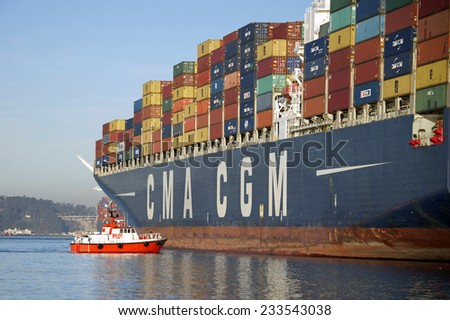OAKLAND, CA - NOVEMBER 25, 2014:  P/V GOLDEN GATE PILOT on the port bow of CMA CGM LYRA assisting with the Cargo Ships departure from the Port of Oakland. - stock photo