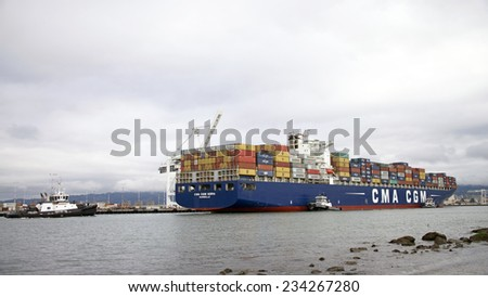 OAKLAND, CA - NOVEMBER 29, 2014: The Port of Oakland's narrow Inner Harbor channel is 50 feet deep to accommodate the large Cargo Ships. Multiple Tugboats work together  to guide the ships safely.
