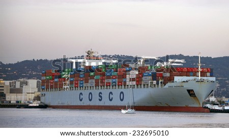 OAKLAND, CA - NOVEMBER 23, 2014: Tugboats move vessels that should not move themselves, such as ships in a crowded harbor. Multiple Tugboats escort COSCO KAOHSIUNG Cargo Ship from the Port of Oakland.