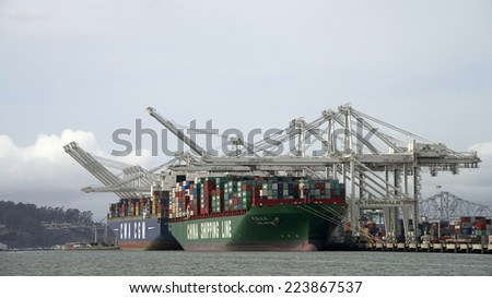 OAKLAND, CA - OCTOBER 15, 2014: Loading cargo at the port of Oakland, CMA CGM, a French container ship is docked next to a China Shipping Line Cargo ship, based out of Shanghai, China.