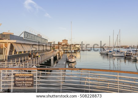 Oakland, CA, USA - July 30, 2016: Jack London Square harbor with sunset. Jack London Square is a popular entertainment and business destination on the waterfront of Oakland, California