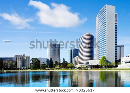 Oakland, California. View across Lake Merritt with beautiful reflections of buildings on the water's edge.  There is a blimp in the sky.