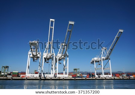 OAKLAND - OCTOBER 12: Row of Cargo Cranes tower over shoreline in Oakland Harbor, Fourth busiest container port in the country.  Oakland California October 12, 2015. - stock photo